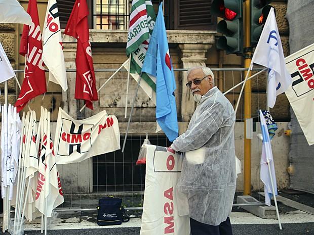 Médico desenrola banner durante protesto em frente ao Ministério da Economia, em Roma (Foto: Alessandro Bianchi/Reuters)
