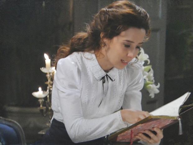 Laura percebe que o poema citado por Isabel está em seu livro (Foto: Lado a Lado / TV Globo)