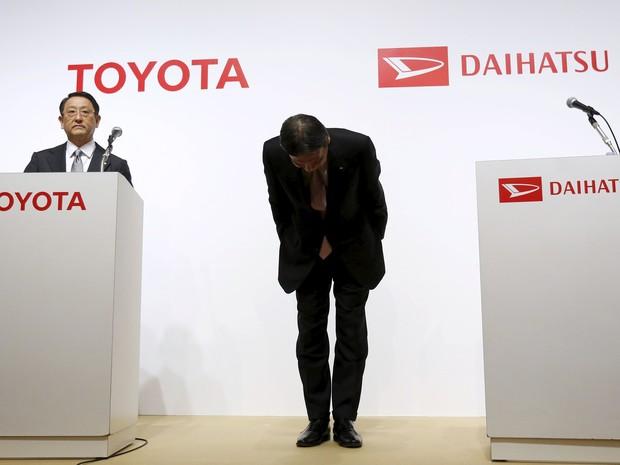 Presidente da Daihatsu, Masanori Mitsui, se curva ao lado do presidente da Toyota, Akio Toyoda, durante anúncio da aquisição em Tóquio (Foto: REUTERS/Yuya Shino)