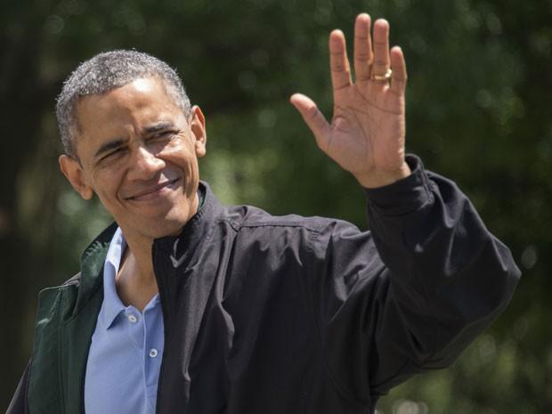 Obama acena neste domingo (4) após retornar de Camp David, a residência presidencial de veraneio, onde passou parte do final de semana (Foto: Jim Watson/AFP)