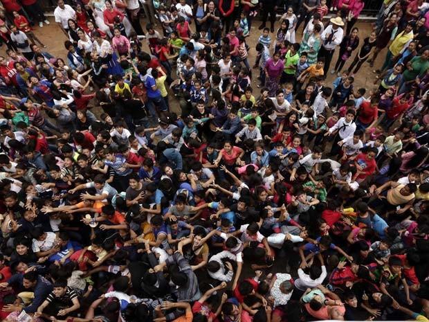 Jovens e crianças se aglomeram para pegar notas jogadas de igreja na festa Natividade de Maria nesta segunda-feira (7) no Paraguai (Foto: AP Photo/Jorge Saenz)