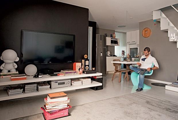 A parede pintada de preto disfarça a tevê e dá profundidade à sala. Sentado na cadeira Panton, da Micasa, está o arquiteto Mauricio Karam, dono do apartamento e autor do projeto. Tapete da By Kamy (Foto: Edu Castello )