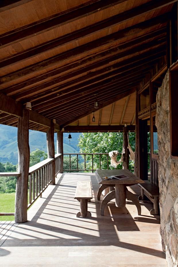 Varanda | Na altura da copa das árvores, a área é coberta pelo telhado prolongado. Como fica ao lado da cozinha, tem uma mesa de refeições e bancos de madeira bruta (Foto: Marco Antonio/Editora Globo)