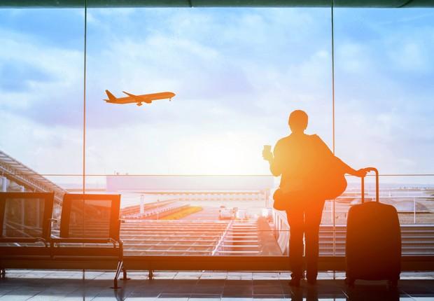 Viajante aguardando no aeroporto com avião ao fundo (Foto: Thinkstock)
