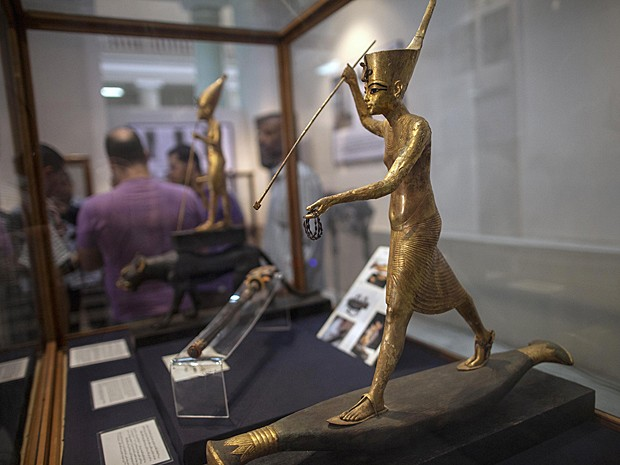 Estátua da 18ª dinastia mostra o rei Tutankhamon em pé sobre barco de papiro em exposição no Museu Egípcio, no Cairo (Foto: Mahmoud Khaled/AFP)
