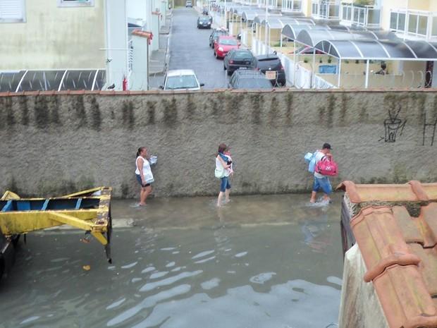 Pessoas tiveram dificuldades para andar em uma das ruas do bairro Vila São Jorge, em São Vicente (Foto: Jonatas Oliveira/G1)