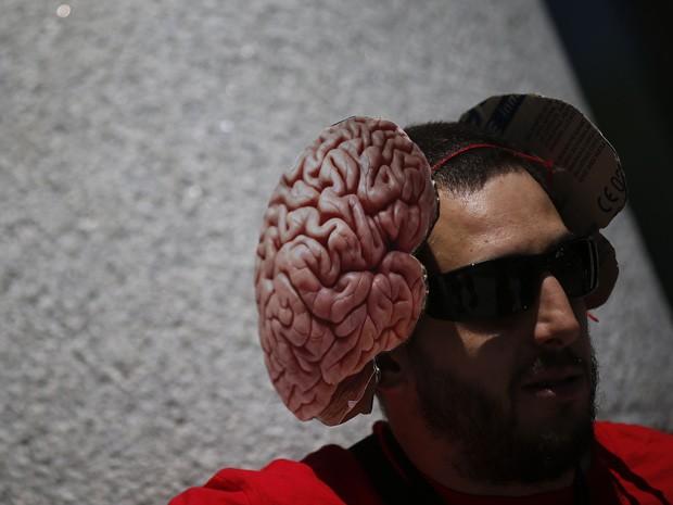 Pesquisador exibe chapéu de cérebro durante um protesto na Espanha (Foto: Susana Vera/Reuters)