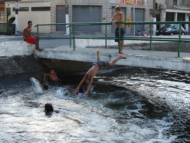 Crianças brincam dentro de canal em Santos (Foto: André Souza / VC no G1)