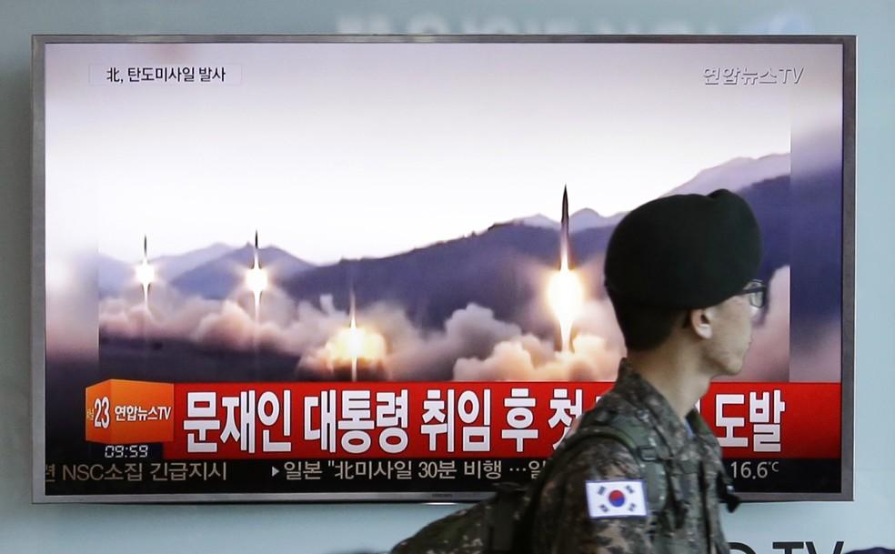 Soldado do Exército da Coreia do Sul passa próximo a TV que exibia lançamento de míssil feito pela vizinha Coreia do Norte (Foto: Ahn Young-joon/AP)