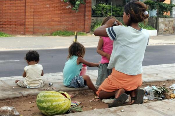 Mulher cuida dos filhos em uma rua de Assunção, no Paraguai. País é um dos mais afetados pela pobreza na região (Foto: Andrés Cristaldo/EFE)
