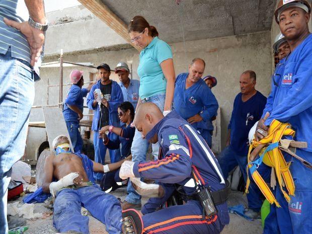 Operário ajuda no atendimento enquanto outro segura equipamentos que romperam (Foto: Marina Fontenele/G1 SE)