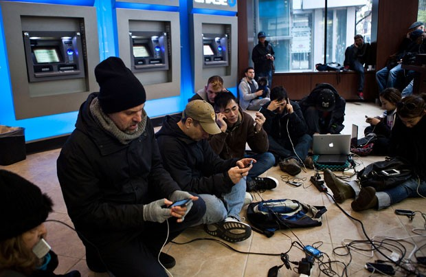 Pessoas se reúnem em volta de uma tomada em caixa de banco em Manhattan. (Foto: Andrew Burton/Getty Images/AFP)