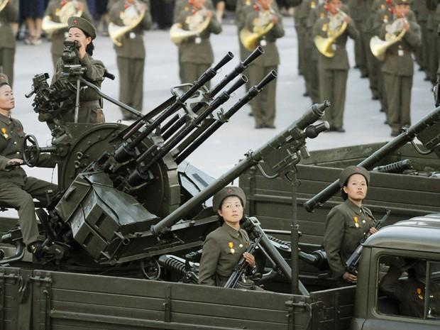 Soldados mulheres com a arma de artilharia antiaérea da Coreia do Norte durante desfile militar, em 2008 (Foto: Kyodo News/AP)