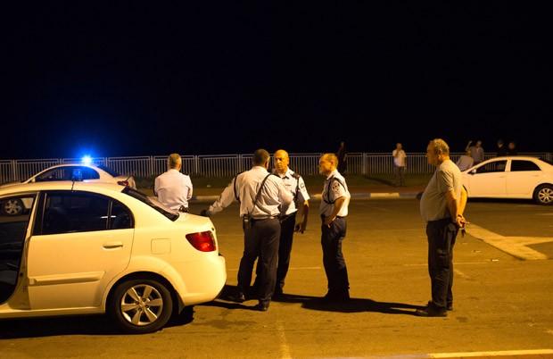 Policiais em frente ao mar em Jaffa, região de Tel Aviv, na noite desta quinta-feira (15), próximo ao local em que o foguete teria caído (Foto: AFP)