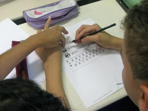 Hércules Antunes, de 12 anos, faz exercício com uma professora exclusiva na sala de aula da Emef Pedro Navas (Foto: Ana Carolina Moreno/G1)