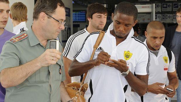 Eto'o dá autógrafo no Anzhi ao lado de Roberto Carlos (Foto: Divulgação)