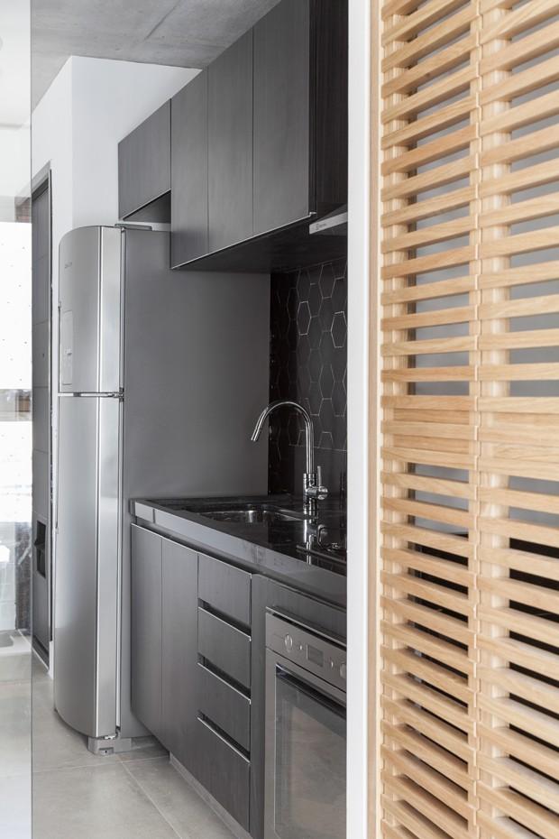 Na cozinha, armários em Formica ebanizada desenhados pelo escritório Now. A parede acima da pia foi revestida com ladrilho hidráulico hexagonal da Dalle Piagge (Foto: Julia Ribeiro/Divulgação)