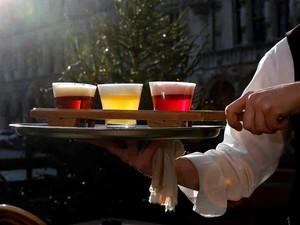 Garçom leva cervejas com as cores da bandeira da Bélgica, em Bruxelas (Foto: Francois Lenoir/Reuters)