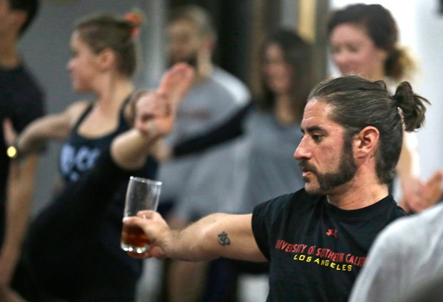 Reed Patterson segura pint de cerveja durante aula de ioga na cervejaria Platform Beer, em Cleveland (Foto: Tony Dejak/AP)