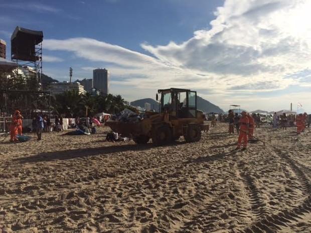 Garis usavam retroescavadeira para retirar lixo deixado durante o réveillon (Foto: Alba Valéria Mendonça/G1)
