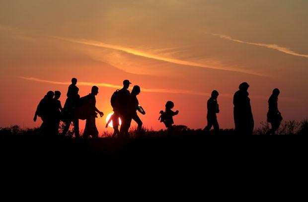 Imigrantes andam após entrarem na Hungria pela fronteira com a Sérvia perto de Roszke neste domingo (30) (Foto: Bernadett Szabo/Reuters)