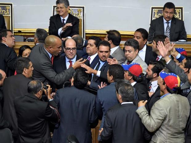 Deputados opositores e chavistas discutem nesta terça-feira (5) durante fala do deputado Julio Borges (centro) na cerimônia de posse da nova Assembleia da Venezuela (Foto: AFP PHOTO/JUAN BARRETO)