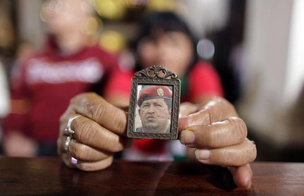 Mulher segura imagem de Chávez ao rezar pelo presidente em igreja de Caracas, nesta segunda-feira (31) (Foto: Ariana Cubillos/AP)