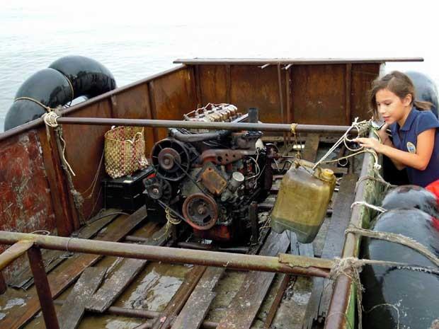 Menina observa embarcação que tinha um motor de trator como propulsor. (Foto: David Adams / Reuters)