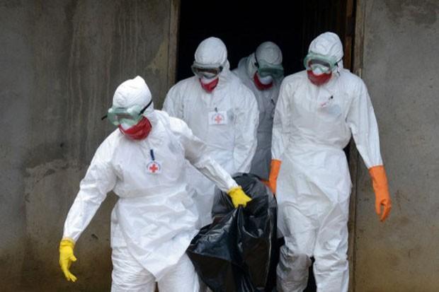 Funcionários da Cruz Vermelha usam roupa especial para retirar corpo de vítima do ebola em Monrovia, na Libéria. A imagem foi feita nesta quinta-feira (4). (Foto: Dominique Faget/AFP)