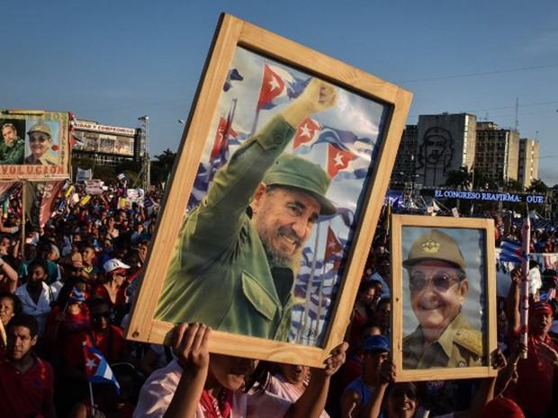 Cubanos mostram fotografias do ex-presidente Fidel Castro e do atual, Raúl Castro, na festa do 1º de maio (Foto: Adalberto Roque / AFP)