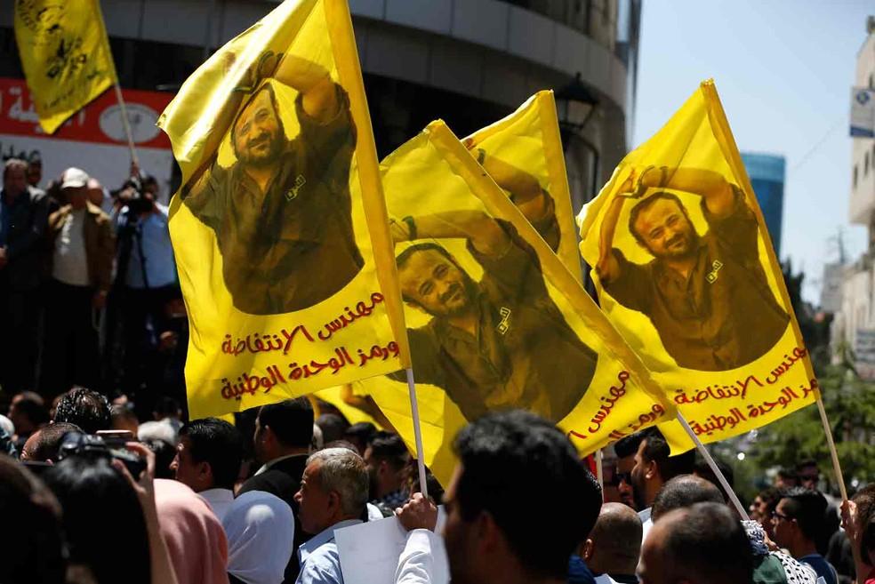 Manifestantes carregam bandeiras com a foto do palestino Marwan Barghouti, pisioneiro que convocou greve de fome  (Foto: Abbas Momani/AFP)