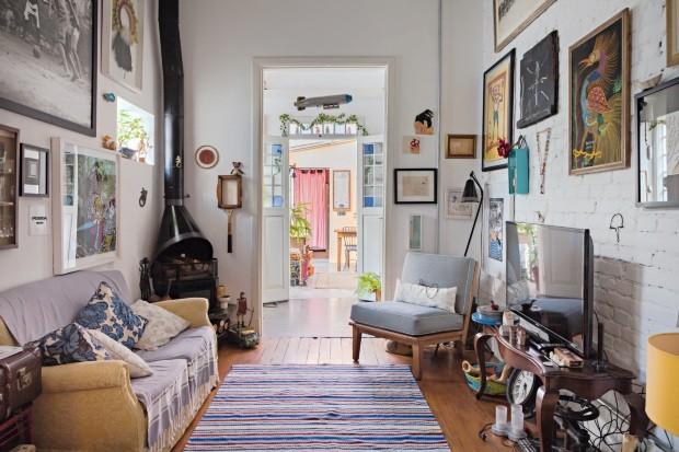 Na parede da sala, os quadros mostram como a moradora é cercada de amigos talentosos e lembranças de família (Foto: Lufe Gomes / Editora Globo)