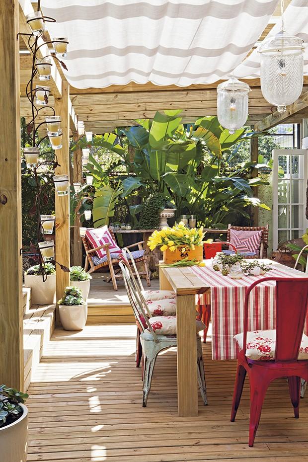 Utilizada para refeições mais demoradas e especiais, a mesa de jantar do terraço tem cadeiras de latão com almofadas florais. Molheiras trazidas de um antiquário em Punta del Este são usadas como vasinhos para os tostões. A caixa de vinho, à esquerda, virou cachepô para as tulipas. Casa da produtora de eventos Lica Paludo (Foto:  Lufe Gomes/Casa e Jardim)