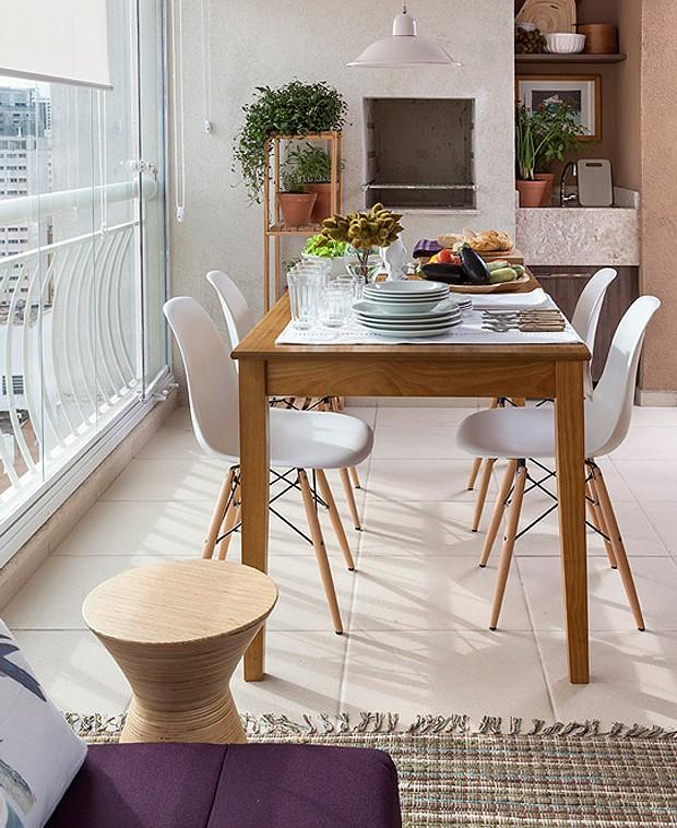 A mesa de madeira clara faz com que os moradores recebam os convidados com muito mais conforto na varandinha! Todos os móveis do espaço são Tok & Stok (Foto: Divulgação)