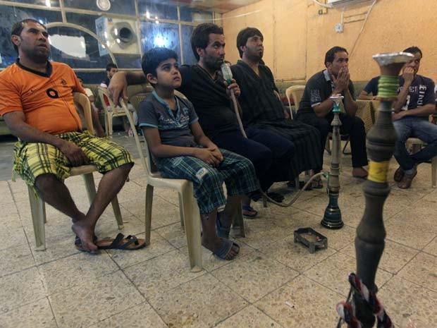 Raad Abdul Hussein (terceiro à esquerda) assiste a jogo da Copa do Mundo com seus amigos em um café de Bagdá (Foto: AFP PHOTO/Ahmad Aa-Rubaye)