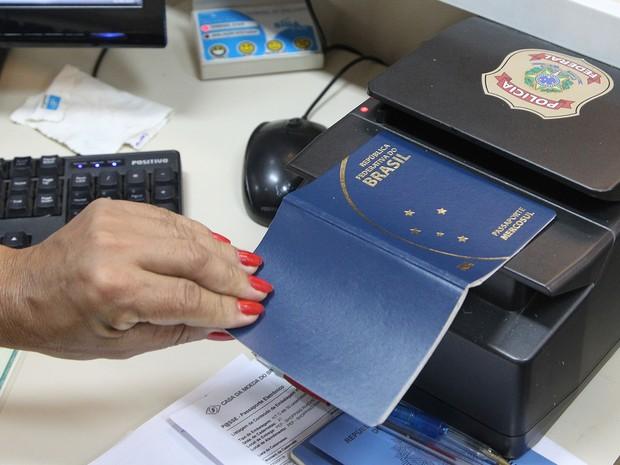 Servidora da Polícia Federal passa passaporte por scanner (Foto: Toninho Tavares/Agência Brasília)