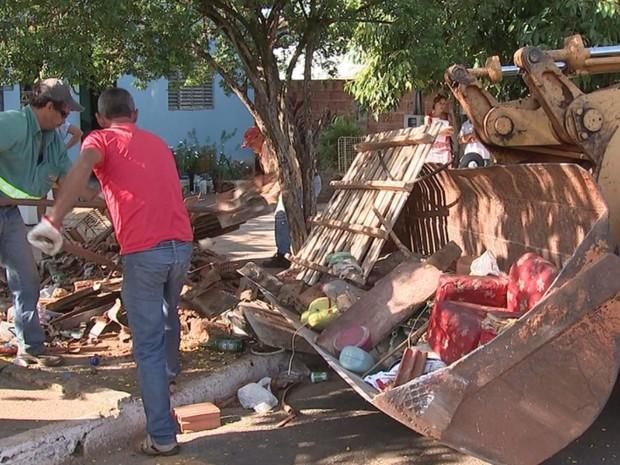 Funcionários de Olímpia fazem limpeza em casas da cidade (Foto: Reprodução/TV TEM)