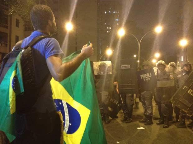 Manifestantes se posiciona diante de PMs (Foto: G1)
