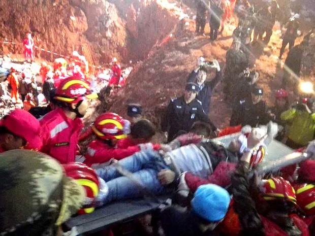Equipes de resgate retiram jovem de 19 anos que foi encontrado vivo nesta quarta-feira (23) no local de deslizamento de terra que cobriu uma grande área em Shenzhen, na China, no domingo (20) (Foto: AFPO)