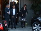 Carla Bruni deixa hotel carioca com look sóbrio e sapato confortável