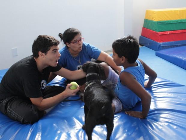 Rodrigo é estimulado pelos monitores por brincadeiras com a cadelinha (Foto: Natália Souza/G1)
