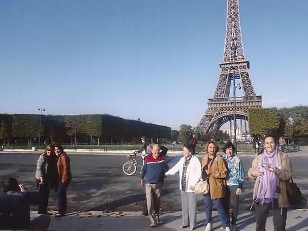 Márcia com um grupo de idosos visitando a Torre Eiffel, na França (Foto: Divulgação)