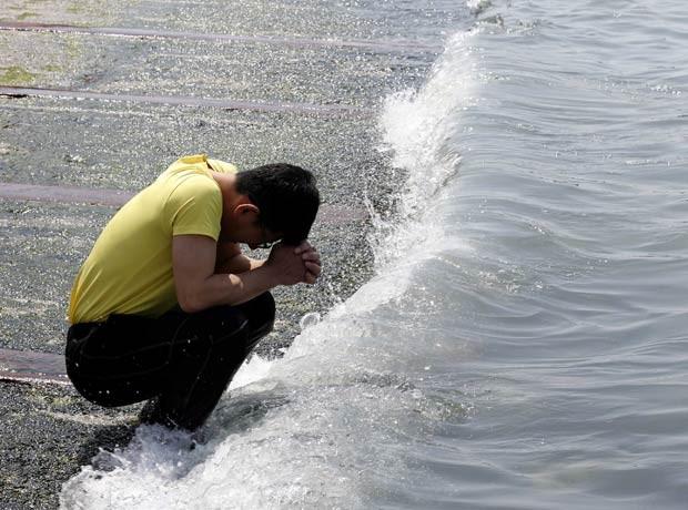 Homem faz orações por desaparecidos à beira do mar em Jindo (Foto: Kim Kyung-Hoon/Reuters)