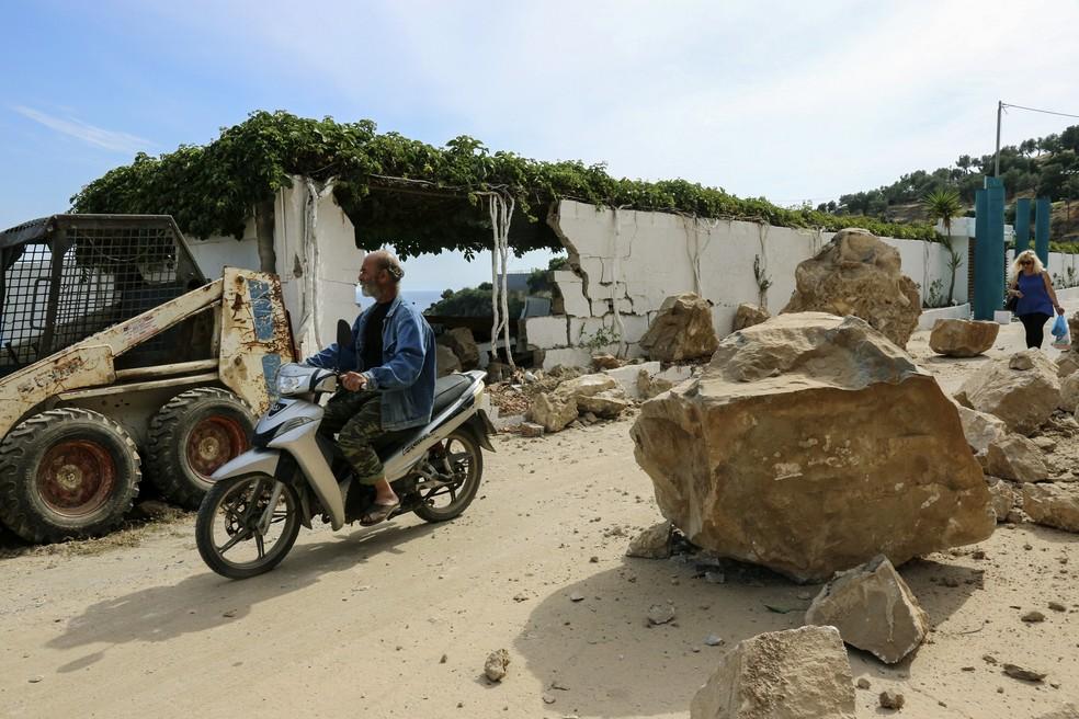 Motociclista passa por destroços provocados por terremoto nesta segunda-feira (12) em Lesbos, na Grécia (Foto: STRINGER / AFP)