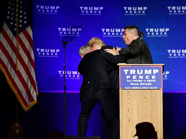 Donald Trump é retirado do palco por agentes durante comício em Nevada, nos EUA, neste sábado (5). (Foto: REUTERS/Steven Styles)