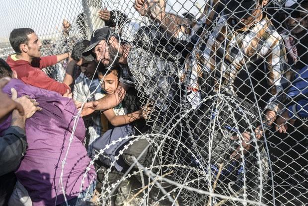 Criança fugindo da guerra na Síria é carregada pela cerca na fronteira com a Turquia neste domingo (14) (Foto: Bulent Kilic/AFP)