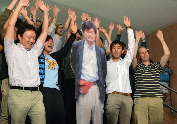 Estudantes do laboratório de Hiroshi Amano, em Nagoia, fazem três vivas para celebrar o Nobel ganho pelo professor, representado numa impressão em tamanho real (Foto: Kyodo News/AP)