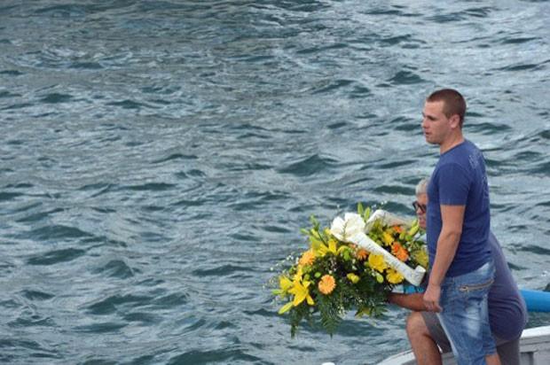 Pescador se prepara para lançar flores ao mar, em homenagem aos mortos do naufrágio ocorrido na costa de Lampedusa (Foto: Alberto Pizzoli/AFP)