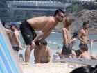 Rodrigo Hilbert vai a praia com um dos filhos gêmeos