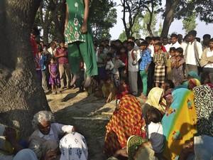 Moradores da vila de Katra se reúnem nesta quarta-feira (28) ao redor dos corpos das duas garotas estupradas e mortas. (Foto: Associated Press)